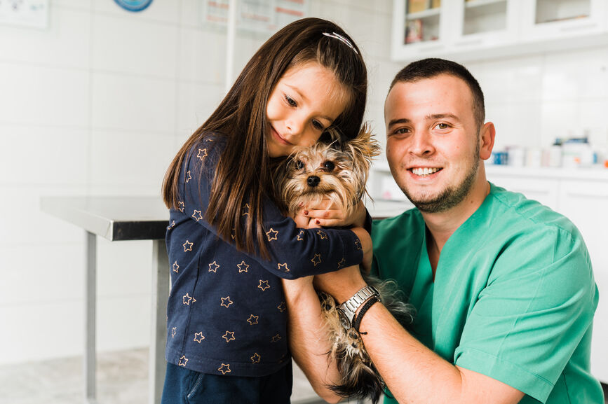 girl hugging small dog with veterinarian