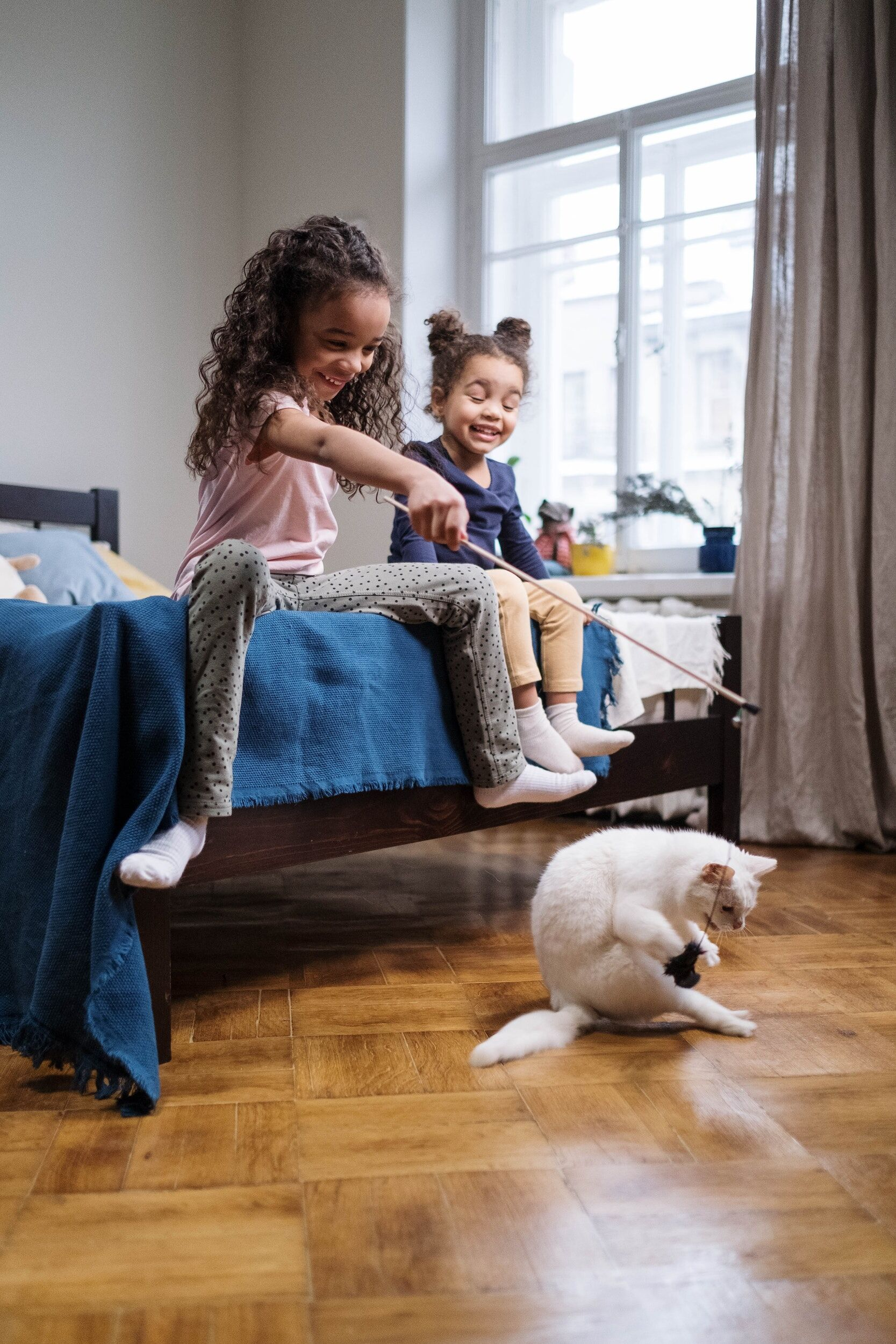 two small children playing with cat and toy wand