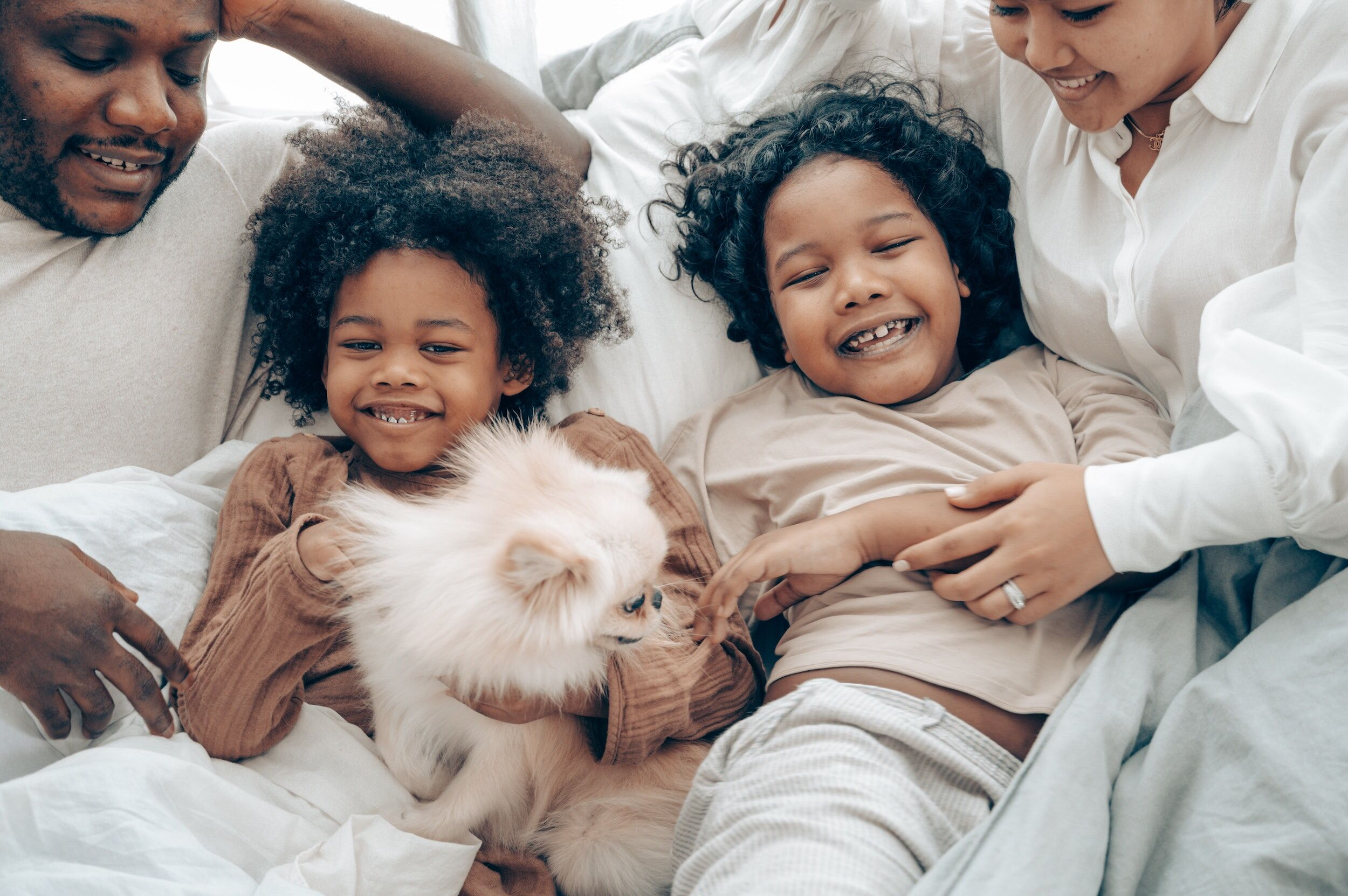 family with dog in bed